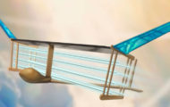 A new MIT plane is propelled via ionic wind. Batteries in the fuselage (tan compartment in front of plane) supply voltage to electrodes (blue/white horizontal lines) strung along the length of the plane, generating a wind of ions that propels the plane forward. Image: MIT