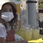 Little girl holds lemonade stand to buy stuffed animals for kids in need -
